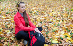 Tourist girl sitting on a  glade of yellow leaves Stock Image
