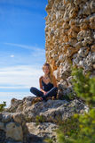Tourist girl sitting near an ancient tower of stone. Beautiful and young girl sits near a tourist ancient stone tower on a sunny day Royalty Free Stock Photo