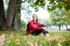 Tourist girl sitting near the autumn maple tree Stock Images