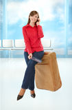 Tourist girl sitting on a suitcase Royalty Free Stock Images