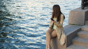 Woman with smart phone enjoy city and river view. Tourist girl with smart phone enjoy city and river view, look around stock video