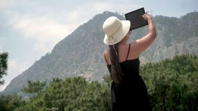 Tourist girl standing near a small green forest and a high hill, holding a gadget and taking pictures stock video footage
