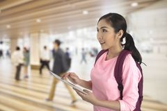 Tourist girl using computer tablet finding traveling information. Tourist girl standing on walkway in building using computer tablet finding traveling Stock Images