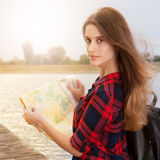 Tourist. Girl standing on a wooden bridge holding a map of the city. Solar flare. Sunny weather, hot summer royalty free stock photos