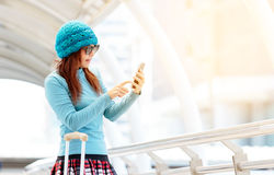 Tourist girl with suitcase use mobile phone in the train station Stock Image