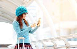 Tourist girl with suitcase use mobile phone Stock Image
