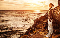 Tourist girl on sunset on the cliff Royalty Free Stock Photos