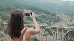 Tourist Girl Taking Photo By Phone of The Bridge Djurdjevic In Montenegro, Travel Lifestyle. Tourist Girl Taking Photo By Phone of The Bridge Djurdjevic In stock footage