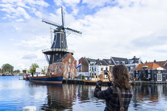 Tourist girl is taking pictures of Dutch windmill Stock Photo