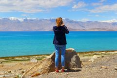Tourist girl taking pictures of mountain landscape on phone while traveling royalty free stock photo