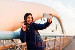 Tourist girl taking a self portrete standing on a famous bridge Stock Photos