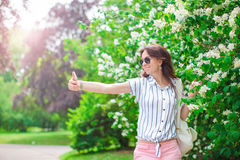 Tourist girl taking travel photos with smartphone on summer holidays. Young attractive tourist taking selfie photo with Royalty Free Stock Images