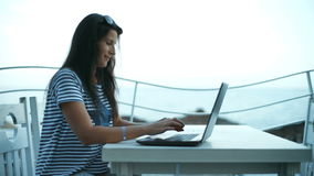 Tourist girl using a laptop on summer vacation in a snack bar terrace on the beach. Tourist girl using a laptop on summer vacation in a snack bar terrace on the stock video