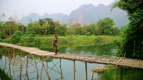 Tourist girl walking on bamboo bridge,vang vieng,laos stock video footage