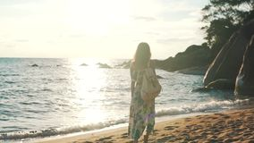 Tourist girl walking by the ocean with a backpack stock video footage