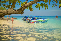 Tourist girl walking on a paradisiac beach next speed boat Royalty Free Stock Image