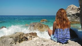 Tourist girl watching sea waves crushing on the rocks in slow motion. Girl in front of a sea wave near rocks recorded in slow motion stock video footage