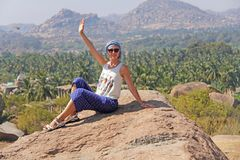 A tourist girl waving her hand at Hampi. A young girl with a covered head sits on a stone and smiles against a background. Of banana plantations. Vijayanagar royalty free stock photo