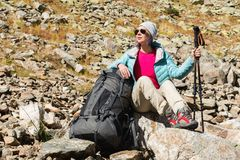A tourist girl wearing sunglasses down jacket and hat with a backpack and mountain equipment with handles for tracking Stock Photography