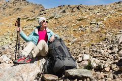 A tourist girl wearing sunglasses down jacket and hat with a backpack and mountain equipment with handles for tracking Royalty Free Stock Images