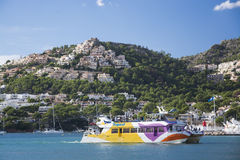 Tourist glass bottom boat and homes perching on the hills above Stock Photo