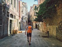 Tourist goes a view with his back to Venice, Italy with an orange backpack and camera on his neck along the old streets Stock Photos