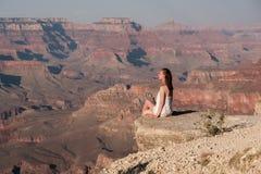 Tourist at Grand Canyon. Sitting on the rock edge, Arizona, USA Stock Images