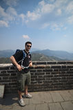 Tourist in Great Wall, China. Western man in the Chinese Great wall and the Chinese flag in the background Royalty Free Stock Photo
