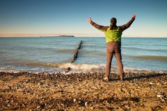 Tourist in green black clothing with hands in the air along beach. Vivid and strong vignetting effect. Stock Images