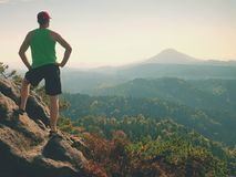 Tourist in green singlet and black shorts on rock, enjoy nature scenery. Valley in sun bath Royalty Free Stock Image