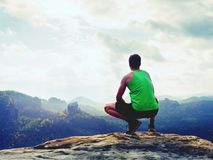 Tourist in green singlet and black shorts in squatting position on a rock, enjoy scenery. Royalty Free Stock Photos