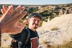 The tourist greet another tourist with a gesture of the hand. Hiking in the mountains.  royalty free stock photos