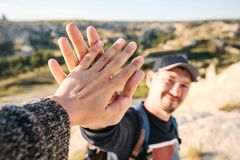 The tourist greet another tourist with a gesture of the hand. Hiking in the mountains. Selective focus. The tourist greet another tourist with a gesture of the royalty free stock photography