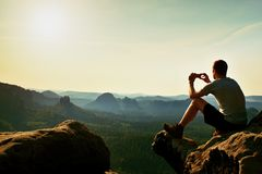 Tourist in grey t-shirt takes photos with smart phone on peak of rock. Dreamy hilly landscape below, orange pink misty sunrise in Stock Photos