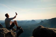 Tourist in grey t-shirt takes photos with smart phone on peak of rock. Dreamy hilly landscape below, orange pink misty sunrise in Royalty Free Stock Images