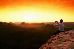 Tourist in grey t-shirt takes photos with smartphone on rocky peak Stock Image