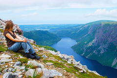 Tourist at Gros Morne Summit. Famale admiring Ten Mile Pond from Gros Morne Summit in Newfoundland, Canada Stock Image