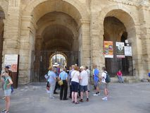 Tourist group outside Roman amphitheatre. A tourist group gather outside the Roman amphitheatre in the city of Arles in Provence, France Stock Image