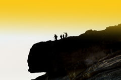 Tourist group on the top of the cliff. Travel activities: hiking. Silhouettes of the explorers on the cliff. Travel activities: hiking, climbing, diving Stock Photo
