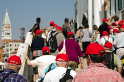 Tourist Group in Venice. VENICE, ITALY - JUNE 8: A group of red capped tourists being led across a crowded bridge in Venice on June 8 2013.  The main routes Stock Photo