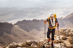 Tourist guide backpacker walking running mountain cliff desert,. Tourist man guy guide mountaineer walking stone trail cliff using poles sticks, hiking trekking stock photography