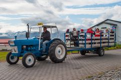 Tourist guide driving a tractor pulling a wagon with tourists royalty free stock image