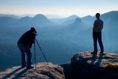 Tourist guide and photo enthusiast stay with tripod on cliff and thinking. Dreamy fogy landscape, blue misty sunrise in a beautifu Royalty Free Stock Photos