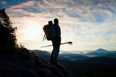 Tourist guide with pole in hand. Hiker with sporty backpack stand on rocky view point above misty valley. Sunny spring daybreak Royalty Free Stock Images
