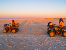 Tourist and guide on quad bikes stop while crossing Makgadikgadi Stock Photos