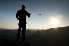 Tourist guide show the right way with pole in hand. Hiker with sporty backpack stand on rocky view point above misty valley. Sunny Royalty Free Stock Photos