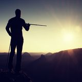 Tourist guide show the right way with pole in hand. Hiker with sporty backpack stand on rocky view point above misty valley. Sunny Stock Photos