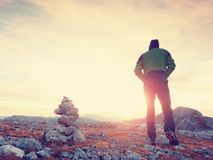 Tourist guide at stocked stones on Alps peak. Strong hiker enjoy sunset in   Alpine mountain. Royalty Free Stock Photos