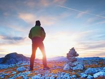 Tourist guide at stocked stones on Alps peak. Strong hiker enjoy sunset in   Alpine mountain. Stock Photos