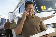 Tourist Guide Talking On Phone. Mature tourist guide talking on phone while holding a book with passengers in background Royalty Free Stock Images